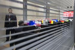 Computer screens showing the national flags of the countries participating in the World Cup 2018 are reflected in a glass-wall as a Russian police officer looks through, at the International Police Cooperation Center opened in Domodedovo, outside Moscow, Russia.