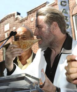 "John Travolta, star of the upcoming film ""Gotti,"" eating a slice of pizza from Lenny's Pizzeria in Brooklyn."