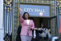 London Breed waves before speaking to reporters outside of City Hall in San Francisco.