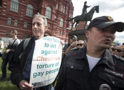 """Russian police detain Gay rights activist Peter Tatchell, center, as he holds a banner that read """"Putin fails to act against Chechnya torture of gay people"""" near Red Square in Moscow, Russia."""