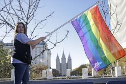 Sandy Newcomb poses for a photograph with a rainbow flag as Mormons gather for a mass resignation from the Church of Jesus Christ of Latter-day Saints in Salt Lake City.