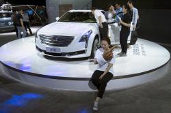 A woman poses for a photo in front of a CT6 Cadillac during the Consumer Electronics Show Asia 2018 in Shanghai, China on Friday, June 15, 2018