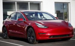 In this May 27, 2018, file photo, a 2018 Model 3 sedan sits at a Tesla dealership in Littleton, Colo.