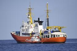 """In this June 12, 2018 file photo, an Italian Coast Guard boat approaches the French NGO """"SOS Mediterranee"""" Aquarius ship as migrants are being transferred, in the Mediterranean Sea"""