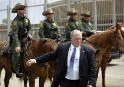 In this May 7, 2018 picture, Thomas Homan, the recently retired acting director of U.S. Immigration and Customs Enforcement, greets border patrol agents along the border with Tijuana, Mexico, in San Diego