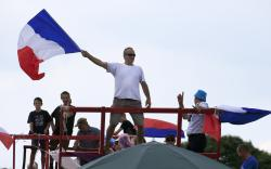 Spectators wave the French flag as they wait for the pack to pass during the fourth stage of the Tour de France cycling race over 195 kilometers (121 miles) with start in La Baule and finish in Sarzeau, France.