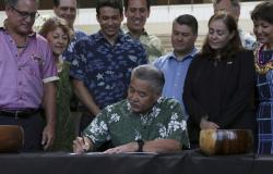 Hawaii Gov. David Ige signs legislation banning the sale of sunscreens containing two chemicals believed to harm coral reefs.