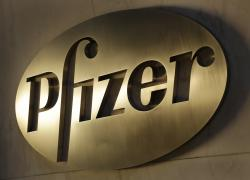 The Pfizer logo is displayed at world headquarters in New York. Pfizer says it's going to reorganize the company into three businesses.