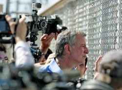 New York City Mayor Bill de Blasio looks through a closed gate at the Port of Entry facility, in Fabens, Texas.