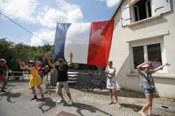 People wave as they wait for the riders to pass during the fifth stage of the Tour de France cycling race over 204.5 kilometers (127 miles) with start in Lorient and finish in Quimper, France.