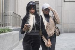 Shannade Clermont, right, and her twin sister Shannon leave Federal court in New York after her arraignment.