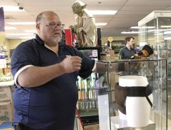 """Blockbuster Alaska General Manager Kevin Daymude moves a display case featuring the jockstrap worn by actor Russell Crowe in the 2005 movie """"Cinderella Man"""" at a Blockbuster video store in Anchorage, Alaska."""