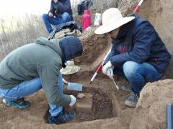 In this Sunday, Dec. 10, 2017 photo provided by Zhaoyu Zhu, scientists examine a pointed piece of quartzite rock that was unearthed from the oldest layer of dirt at a site in the Loess Plateau in China