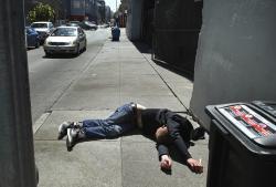 A man lies on the sidewalk beside a recyclable trash bin in San Francisco.