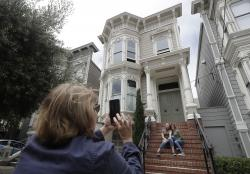 "Aries Layton, seated left, and her aunt Kelsy Layton pose as Debra Layton, Aries' grandmother and Kelsy's mother, foreground, takes photos outside a Victorian home made famous by the television show ""Full House"" in San Francisco."