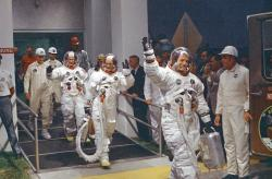 In this 1969 file photo, Neil Armstrong waving in front, heads for the van that will take the crew to the rocket for launch to the moon at Kennedy Space Center in Merritt Island, Fla.
