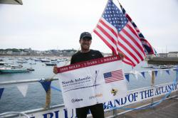 In this Saturday, Aug. 4, 2018 photo provided by Bryce Carlson Adventures, Bryce Carlson poses for a photo after completing his solo unsupported row across the Atlantic, at St Mary's Harbour, Isle of Scilly, England.