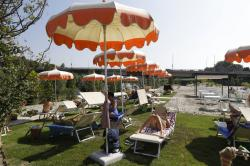 """Sunbathers sit on the sun beds on the newly opened """"Tiberis"""" beach along the Tiber river in Rome."""