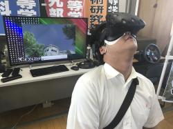 In Friday, Aug. 8, 2018, photo, Namio Matsura, 17-year-old member of the computation skill research club at the Fukuyama Technical High School, watches Hiroshima city before atomic bomb fell in virtual reality experience at the high school in Hiroshima, western Japan