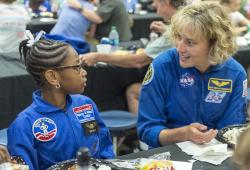 In this July 13, 2018 photo, NASA astronaut Dottie Metcalf talks with space-camp camper Bria Jackson, of Atlanta, before giving a speech at the U.S. Space & Rocket Center in Huntsville, Ala.