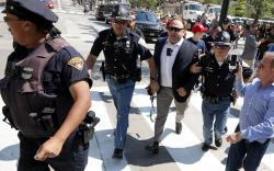 Alex Jones, center right, is escorted by police out of a crowd of protesters outside the Republican convention in Cleveland.