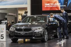 In this Jan. 13, 2017, file photo men look at a BMW 5 series during the media day of the 95th European Motor Show in Brussels
