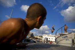Youths jump into the water at the port of Jaffa, Israel.