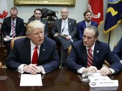 In this Feb. 16, 2017, file photo Republican U.S. Rep. Chris Collins of western New York state, right, sits next to President Donald Trump.