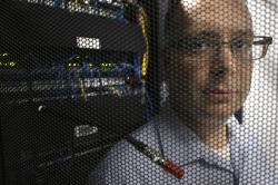In this Wednesday, Aug. 1, 2018, photo Russell Benoit, of Dartmouth, Mass., marketing manager for AVTECH Software, stands behind the door of a server cabinet in the company's data center in Warren, R.I. AVTECH Software, which makes software to control building environmental issues, is preparing for what some say is the wave of the future: laws requiring businesses to be up-front with customers about how they use personal information