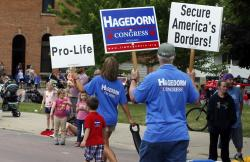 In this June 10, 2018 photo, volunteers for Minnesota 1st District congressional candidate Jim Hagedorn carry signs during a parade in Waterville, Minn.