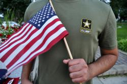 In this July 3, 2018, file photo, a Pakistani recruit, 22, who was recently discharged from the U.S. Army, holds an American flag as he poses for a picture