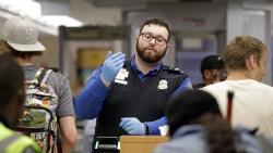 A TSA agent calls passengers forward for screening at Sea-Tac International Airport Friday evening, Aug. 10, 2018, in SeaTac, Wash.