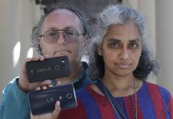In this July 25, 2018 photo, Kalyanaraman Shankari, right, and her husband Thomas Raffill hold their phones while posing for photos in Mountain View, Calif.