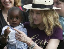In this April 19, 2007 file photo, U.S. singer Madonna carries her Malawian adopted son David Banda in the village of Masekese, Malawi.