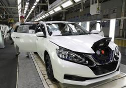 A worker inspects a Nissan Sylphy Zero Emission, Nissan's first all-electric vehicle built in China, at a production line in Guangzhou, Guangdong province, China, Monday, Aug. 27, 2018