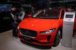 In this April 25, 2018, file photo journalists and visitors look at the Jaguar electric-powered I-Pace model showcases at the China Auto Show during the media day in Beijing