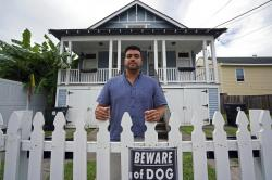 Alex Ramirez poses in front of one of his short-term rental properties that he refurbished from a blighted state, in Mid City New Orleans.