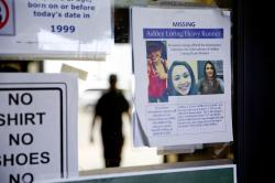 A missing poster for Ashley HeavyRunner Loring is posted to the entrance of a grocery store on the Blackfeet Indian Reservation in Browning, Mont., Thursday, July 12, 2018
