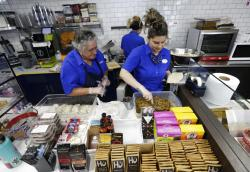 Emma Gonzalez, left, and Lidices Ramos, right, make empanadas at the Mendez Fuel convenience store in Miami.