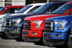 In this Nov. 19, 2015, file photo a row of 2015 Ford F-150 pickup trucks are parked on the sales lot at Butler County Ford in Butler, Pa.