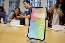 Customers buy the iPhone X at the Apple Store on New York's Fifth Avenue.