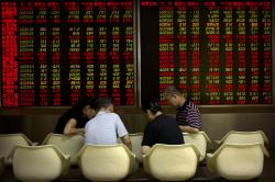 Chinese investors play cards near an electronic display showing stock prices at a brokerage house in Beijing, Tuesday, Sept. 11, 2018