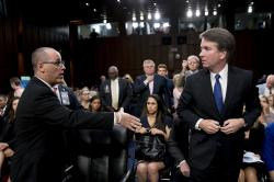 In this Tuesday, Sept. 4, 2018 file photo, Fred Guttenberg, the father of Jamie Guttenberg who was killed in the Stoneman Douglas High School shooting in Parkland, Fla., left, attempts to shake hands with President Donald Trump's Supreme Court nominee, Brett Kavanaugh, right, as he leaves for a lunch break while appearing before the Senate Judiciary Committee on Capitol Hill in Washington to begin his confirmation hearing