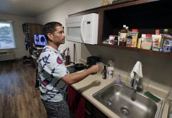 In this Monday, Sept. 10, 2018, photo, Jose Santiago checks on items in the kitchenette in his room at the WoodSpring Suites in Orlando, Fla. Santiago, like many Puerto Rican evacuees, has until Friday to find a place to live
