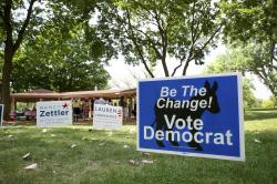 In this July 29, 2018, photo, campaign signs are seen on picnic grounds in Geneva, Ill., where Democratic candidates and their supporters gathered