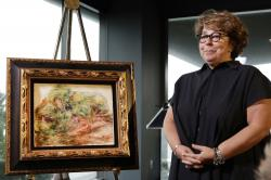 Sylvie Sulitzer, a delicatessen owner from the south of France, stands with a Renoir painting that was returned to her in a reparation ceremony at a news conference, Wednesday, Sept. 12, 2018, in New York