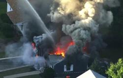 In this image take from video provided by WCVB in Boston, flames consume the roof of a home in Lawrence, Mass, a suburb of Boston, Thursday, Sept. 13, 2018.