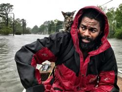 """Robert Simmons Jr. and his kitten """"Survivor"""" are rescued from floodwaters after Hurricane Florence dumped several inches of rain in the area overnight, Friday, Sept. 14, 2018 in New Bern, N.C."""