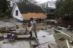 Resident Joseph Eudi looks at flood debris and storm damage from Hurricane Florence at a home on East Front Street in New Bern, N.C., Saturday, Sept. 15, 2018