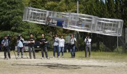In this Saturday, June 3, 2017, file photo, Tsubasa Nakamura, project leader of Cartivator, third from left, watches the flight of the test model of the flying car on a former school ground in Toyota, central Japan